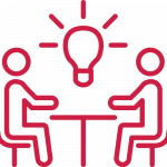 red icon of two figures sitting at a table with a lightbulb representing an idea